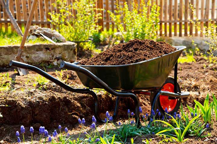 Wheel barrel filled with fresh dug out soil on a landscaping job site